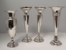 A George V silver bud vase with a flared rim and hammered baluster body and spreading foot,