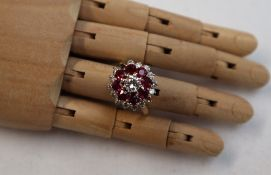 A ruby and diamond dress ring, the central round brilliant cut diamond approximately 0.