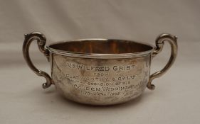 A George V silver twin handled sugar basin, with a line decorated top and scrolling handles,