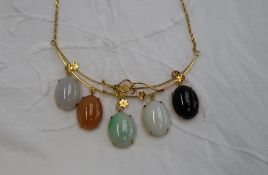 A Chinese yellow metal necklace set with jade and hard stone panels,
