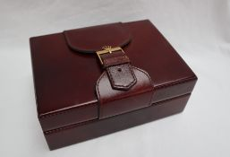 A Rolex burgundy leather watch box, with a buckle top and wooden liner, No.71.00.