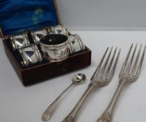 A cased set of six electroplated napkin rings together with continental table forks and a silver