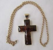 A 9ct yellow gold and amber set cross, approximately 31 grams on a 9ct gold chain,