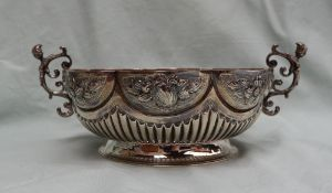 A Victorian silver twin handled lobed bowl decorated with flower heads and fruit with a reeded body