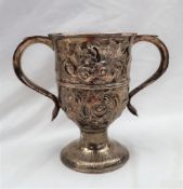 A George III silver twin handled trophy cup, embossed with flowers and leaves on a spreading foot,