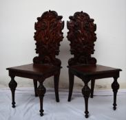 A pair of continental carved oak hall chairs, the back decorated with scrolling leaves and a shell,