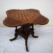 A reproduction mahogany games table, of lobed shape with four drop flaps,