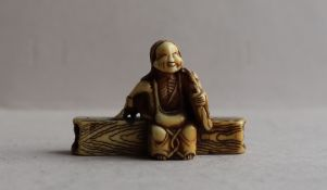 A 19th century Japanese ivory netsuke in the form of an elderly lady seated on a log,