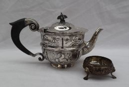 A Victorian silver teapot, the domed top embossed with leaves, above a flared rim,