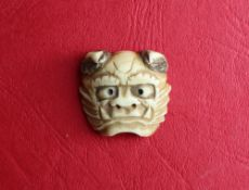 A Japanese stag antler Oni mask netsuke, signed,
