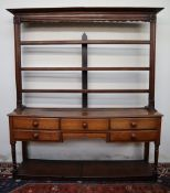 An 18th century South Wales oak dresser, the open rack with a moulded cornice and three shelves,