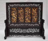 A Chinese hardwood and tortoiseshell table screen, with carved pierced decoration,