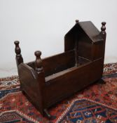 An 18th century oak cot, with a pointed arched top and turned finials, above slat sides on rockers,
