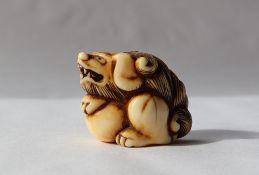 A 19th century Japanese ivory netsuke depicting a shi shi lion dog on a ball,