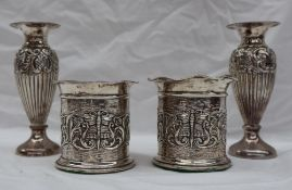 A pair of Edward VII silver vases with flared rims above a cylindrical body embossed with scrolls