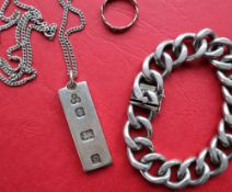 A silver ingot on a chain together with a heavy link silver bracelet, and a silver ring,