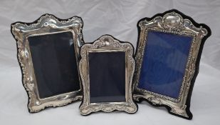 A modern silver photograph frame with a triple arched top decorated with scrolls and leaves,
