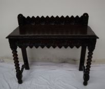 A 19th century carved oak side table, the raised back carved with arched and flowers heads,