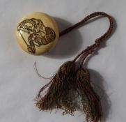 A 19th century Japanese ivory Manju Netsuke, carved with a boy playing with a rat,