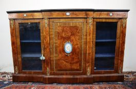 A Victorian walnut credenza the breakfront top with ebonised edge above a central cupboard and two