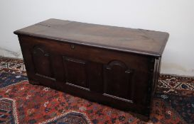 An 18th century oak coffer, the planked rectangular top above a three panelled front on stiles,
