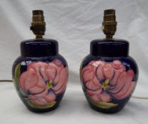 A pair of Moorcroft pottery table lamps, decorated with pink magnolias to a blue ground,
