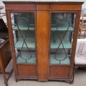 An Edwardian mahogany display cabinet with a pair of glazed doors with glazing bars and glazed