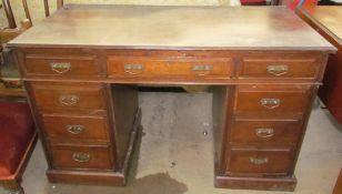 An Edwardian mahogany desk with a rectangular moulded top above a central drawer and two banks of