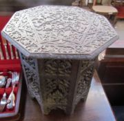 An Anglo Indian hardwood occasional table with an octagonal top and base carved with flowers and