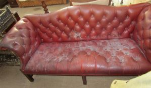 A red leatherette three piece suite with button back upholstery on square legs