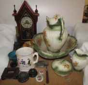 A 19th century steeple clock together with a pottery wash basin set, pottery lions,