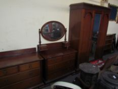 An Edwardian mahogany matched three piece bedroom suite comprising a triple wardrobe,