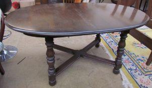 An Ercol dark elm extending dining table