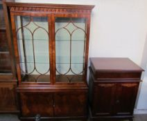 A 20th century mahogany bookcase with a moulded cornice above a pair of glazed doors,