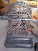 A cast iron umbrella stand with leaf cast decoration and two drip trays