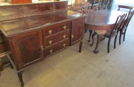 A 20th century mahogany extending dining table with four chairs and a matching sideboard,