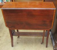 An Edwardian mahogany Sutherland table with a cross banded top and drop flaps on square legs