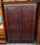 A 19th century mahogany bookcase with a moulded cornice above a pair of cupboard doors on gilt