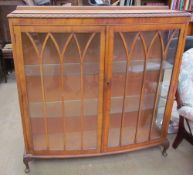 A 20th century walnut display cabinet together with a set of three bar stools