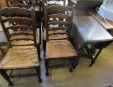 An oak gate leg dining table and four ladder back chairs