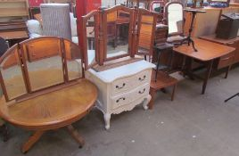 A circular coffee table together with two dressing table mirrors, a white painted chest of drawers,