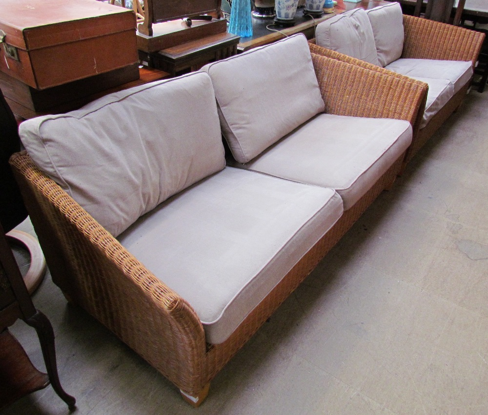 Lot 23 - A wicker upholstered three seater settee with matching two seater example