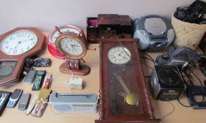 A collection of wall clocks together with radios, pocket knives,