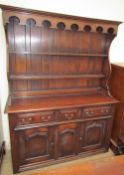 A reproduction oak dining suite including a North Wales style dresser,