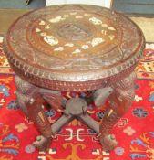 An Indian carved table on elephant head legs,