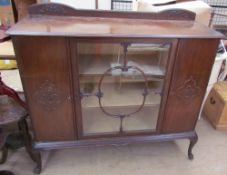 A 20th century mahogany side cabinet with a glazed centre door flanked by two cupboard doors on