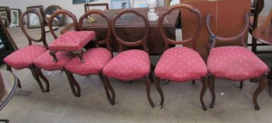 A matched set of six Victorian balloon back dining chairs together with a foot stool