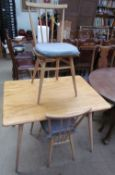 An Ercol style light elm dining table and three chairs