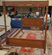 A modern oak four poster king size bed with shaped rails,