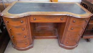 A Victorian mahogany desk with a shaped top inset with leather above a central drawer and two banks